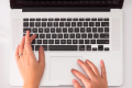 A womans hands typing on a Mac keyboard