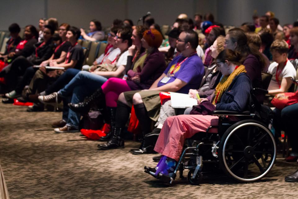 Image of crowd at a panel in colorful clothes and costumes, with a woman in a wheelchair at the end.