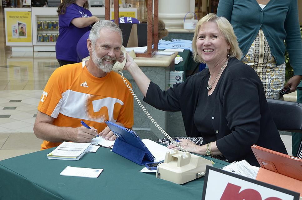 Woman holding up a phone to a man's ear while he writes a check for charity.