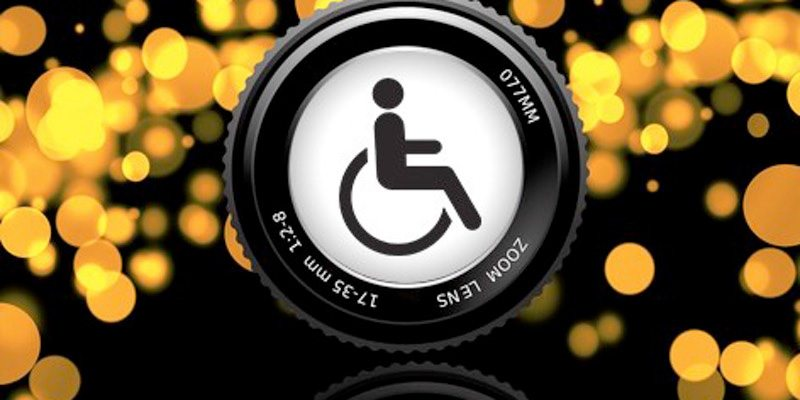 Handicap logo embedded in the center of a camera lense with blurry lights in the background.