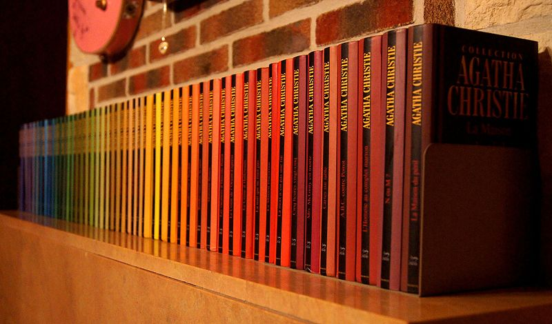 A row of Agatha Christie novels on a mantel piece making muted rainbow effect.