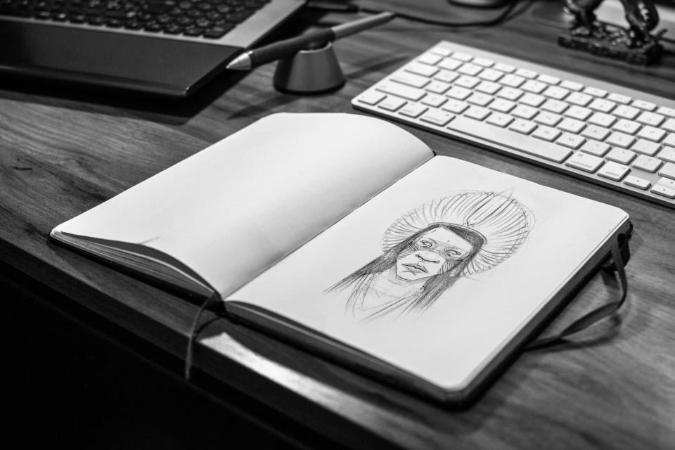 black and white photograph of a sketchbook with an illustration of an indigenous character on a desk