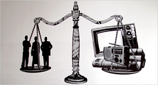 Legal scales overlaid with legal code. Lawyers on one side of the scales adn the other holds a TV, radio and newspaper.