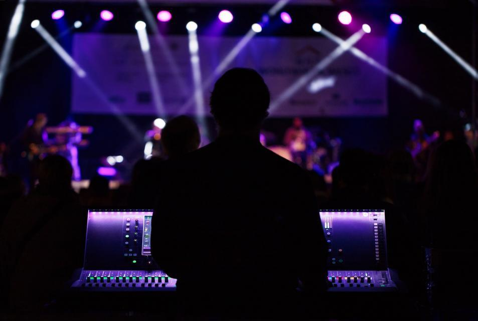 Silhouette of a man in front of a sound board with a concert going on in the background.