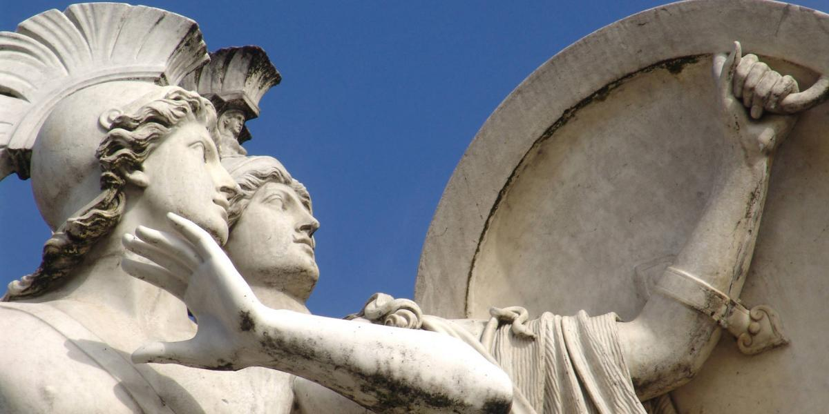 Two Greek Statues behind a stone shield in close-up.