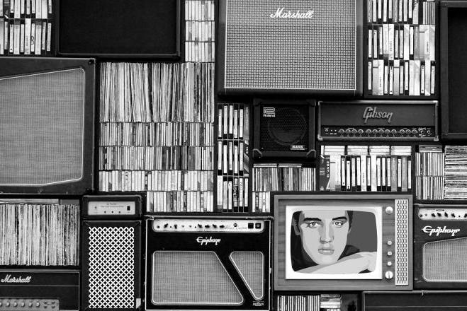 Black and white photo of a wall of antiquated media and amplifiers.