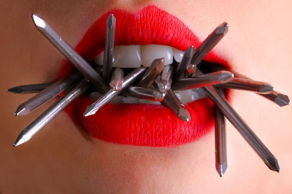 A close up of a woman's lips in bright lipstick with nails coming out of her mouth.