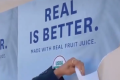 """A hand is tearing off a poster that says """"REAL IS BETTER."""""""